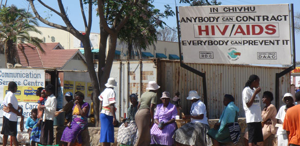 People sitting by an HIV/AIDS awareness sign in Zimbabwe
