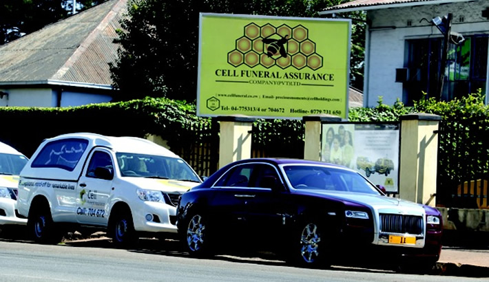 APPARITIONAL... The controversial Rolls Royce Ghost owned by businessman Frank Buyanga and parked at his Cell Funeral Assurance offices along new hearses in Harare's Herbert Chitepo Street. (Picture by Daily News)