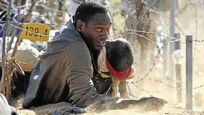 Zimbabwean border jumper slips into South Africa over barbed wire while clutching a child
