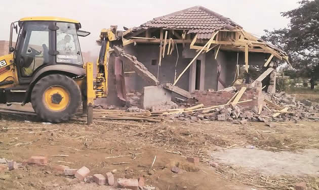 A Harare City Council front-end loader destroys an illegal brick-under-tile house belonging to a Morning Glory Housing Cooperative member in Warren Park D yesterday