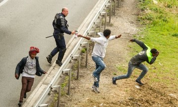 A police officer appears to spray tear gas towards migrants trying to access the Channel Tunnel in Calais Photograph: Philippe Huguen/AFP/Getty Images