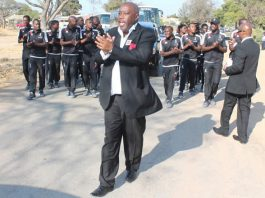 Former Highlanders chairman Ernest Sibanda leads Bosso players in song as they escort a hearse carrying the body of Willard Mashinkila Khumalo to its final resting place on Thursday