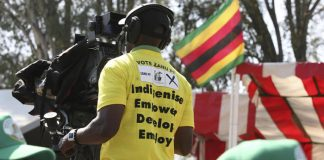 A ZBC cameraman wears a ZANU-PF t-shirt as he covers the President Robert Mugabe's election campaign and manifesto launch at Zimbabwe Grounds in Harare