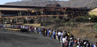 Zimbabwe Iron and Steel Company workers walk to its plant in Redcliff, Kwekwe