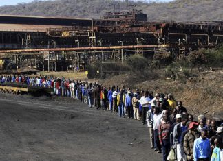 Zimbabwe Iron and Steel Company workers walk to its plant in Redcliff, Kwekwe