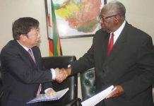 ZMDC board chairman Mr David Murangari (right) and Beijing Pingchang Investments chief representative in Zimbabwe Shouming Lin shake hands after the signing of the Kamativi Tin Mine deal yesterday. — (Picture by Munyaradzi Chamalimba)