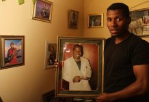 Peter Moyo holds the photograph of his late father, Tongayi Moyo