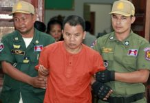 Yem Chroeum (centre), 55, is escorted by Cambodian police officials