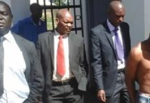 Homicide detectives escort Jackson Moyo at the Mvuma police station in this file photo
