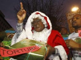 A protester dressed as Father Christmas and wearing a Robert Mugabe mask holds Christmas gifts