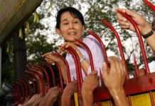 Aung San Suu Kyi being greeted by thousands of supporters over the fence of her house