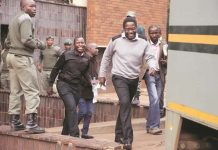 Sunday Mail editor Mabasa Sasa, reporters Brian Chitemba (in brown jacket) and Tinashe Farawo are all smiles after being freed on bail at the Harare Magistrates' Court yesterday.
