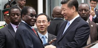 Robert Mugabe shakes hands with Xi Jinping as the Chinese president arrived in Harare last year