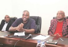 Wicknell Chivhayo stresses a point while flanked by ZIFA president Philip Chiyangwa (right) and board member Edzai Kasinauyo in Harare