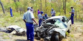 Police officers examine the vehicle involved in a head on collision yesterday