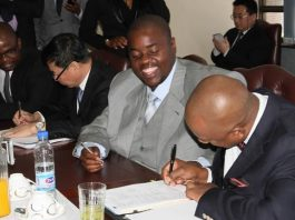 Managing director of Intratrek Zimbabwe Mr Wicknell Chivayo smiles as project director Mr Kevin Makoni signs
