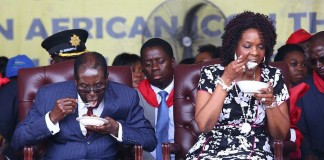 Feast for two: Zimbabwean President Robert Mugabe pictured with his wife Grace eating at his 92nd birthday party on Saturday.