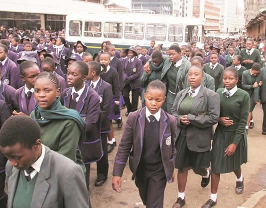 Girls High School and Queen Elizabeth students march during a memorial service for their colleague who was killed by a kombi yesterday. — (Picture by John Manzongo)