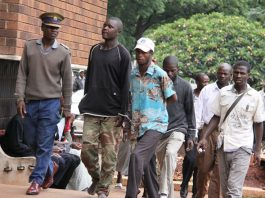 Police escort a robbery suspect in tattered Zimbabwe National Army fatigues to court in Harare in this file picture
