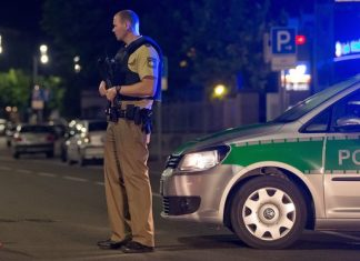 An armed policeman stands guards in Ansbach, Germany, late in Sunday after an explosion. Photograph: Daniel Karmann/EPA