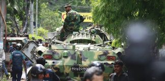 Bangladeshi soldiers and security personnel sit on top of armoured vehicles in a diplomatic zone of the capital, Dhaka. Photograph: AP