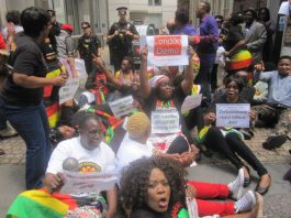 Zimbabwean demonstrators lay down in the road outside the conference in London addressed by Zimbabwe's Finance Minister Patrick Chinamasa preventing him from leaving for more than an hour.
