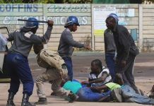 Riot police detain residents of Epworth suburb after a protest by taxi drivers