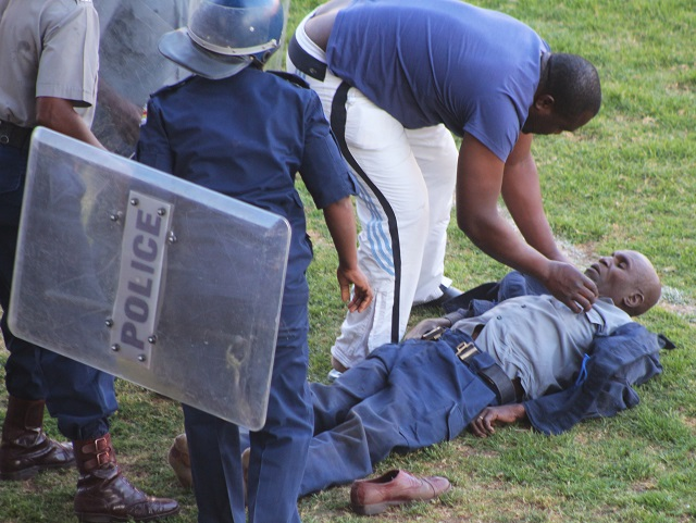 A samaritan attends to an injured Police Officer at Barbourfields Stadium in Bulawayo yesterday.