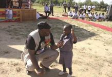 There is growing outrage over a picture showing Local Government minister, Saviour Kasukuwere, forcing a child to execute a Zanu PF slogan.