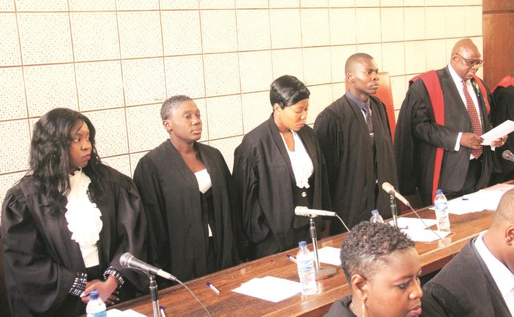 Chief Magistrate Mr Mishrod Guvamombe (right) swears in magistrates (from left) Rumbidzai Dzumbira, Edith Kakuruwo, Nyasha Marufu and Joshua Mawere at the Harare Magistrates' Court on Friday. — Picture by Munyaradzi Chamalimba