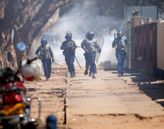 Zimbabwean anti-riot police chase supporters of Zimbabwe Opposition Party Movement for Democratic Change Tsvangirai faction ©Wilfred Kajese (AFP)