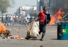 A street vendor flees with his goods as Zimbabwe opposition supporters clash with police in Harare on August 26, 2016 ©Wilfred Kajese (AFP/File)