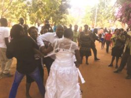 Francisca Kanyama (in wedding dress) is shielded by a Good Samaritan from battering by an irate Magdalene Chamunorwa (partly obscured) outside the Harare Magistrates' Courts yesterday