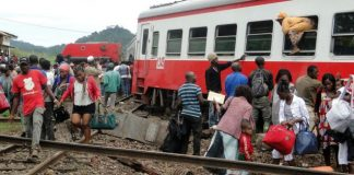 Passengers escape the site of a train derailment in Eseka