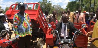Jonathan Moyo dishing out motorbikes for headman and bicycles for village heads in Tsholotsho