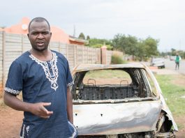 Patson Dzamara near the shell of his burnt out car