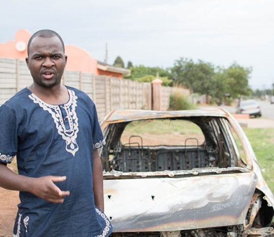 Patson Dzamara near the shell of his burnt out car