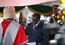 Chief Justice Godfrey Chidyausiku ( red gown) swears in Robert Mugabe as the President of Zimbabwe at the National Sports Stadium in 2013