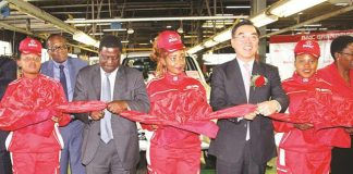 Industry and Commerce Minister Mike Bimha and Chinese Ambassador to Zimbabwe Mr Huang Ping prepare to cut the ribbon at the launch of the first unit of BAIC Pick-up assembled at Willowavale Motor Industries in Harare yesterday. — (Picture by Innocent Makawa)