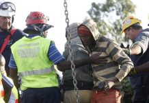 A suspected illegal miner with police and emergency workers at the mine in Benoni, east Johannesburg