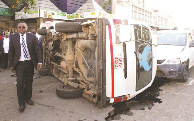 A man walks past a commuter omnibus which overturned after ramming into two other vehicles while reportedly fleeing police in Harare CBD yesterday morning. — (Picture by Memory Mangombe)