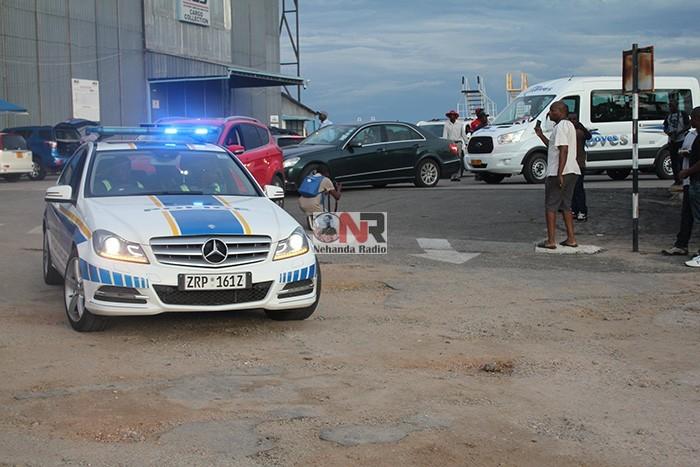 Police escort Morgan Tsvangirai's body from the airport