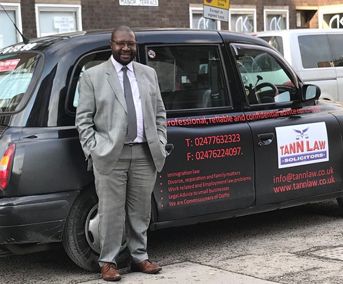 Andrew Nyamayaro standing next to a taxi in Coventry that is advertising their firm Tan Law Solicitors