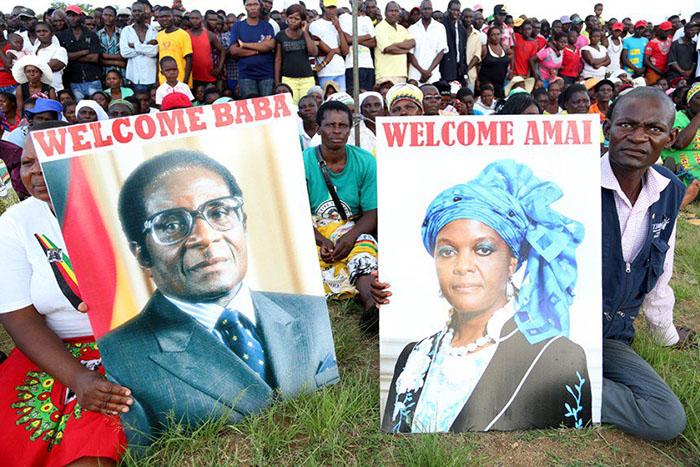 Zanu-PF supporters display posters bearing then President Mugabe and First Lady Grace Mugabe's portraits during a Zanu-PF rally at Chipadze Stadium in Bindura – (Picture by Believe Nyakudjara)