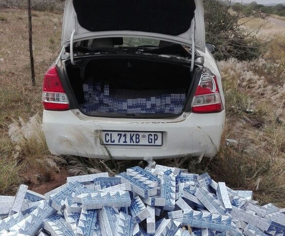 One of the abandoned luxury vehicles and an assortment of smuggled cigarettes