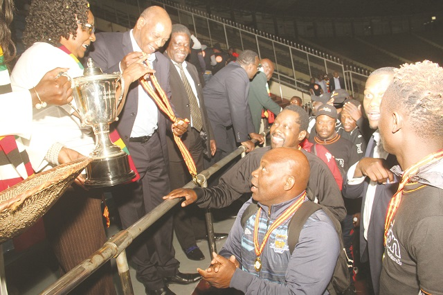 Highlanders coach Madinda Ndlovu receives his winners' medal from Tourism and Hospitality minister Prisca Mupfumira