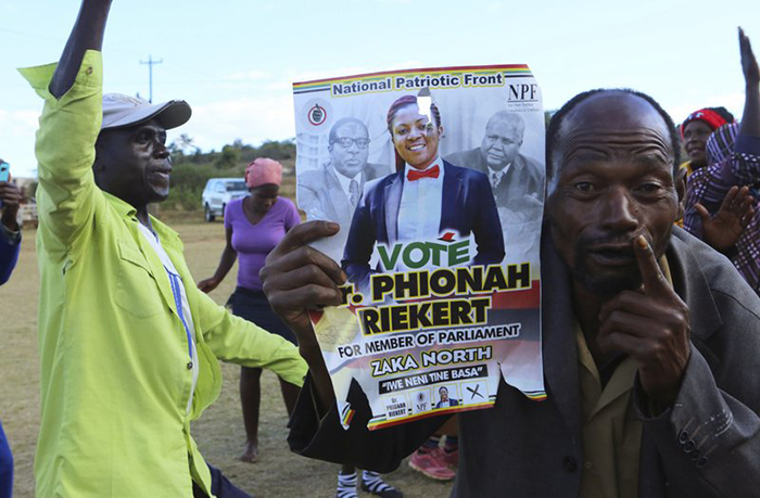 In this Saturday, July 14, 2018, photo, loyalists of Former Zimbabwean Leader Robert Mugabe hold a campaign poster with candidate Phionah Riekert at an election rally in Masvingo, Zimbabwe. The 94-year-old Mugabe, who led the country through 37 turbulent years before a dramatic resignation in November, has emerged as a player ahead of the historic July 30 election _ on the side of the opposition posing a problem for the ruling party he long controlled. (AP Photo/Tsvangirayi Mukwazhi)