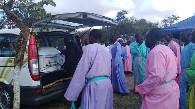 Members of Johane Masowe eChishanu Vadzidzi VaJesu Church prepare to carry a casket bearing the body of their church founder Aaron Mhukuta Gomo, popularly known as Mudzidzi Wimbo, at the gravesite in Goora, Madziwa