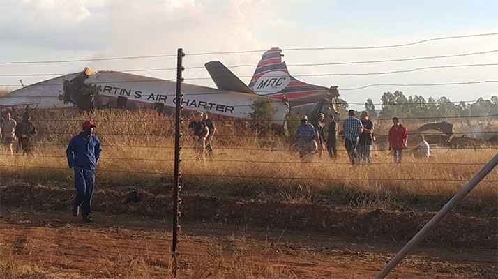 Local emergency services posted a picture on Twitter showing passengers being helped from the burning wreckage of a plane in a grassy field. (Picture via Twitter handle @crimeairnetwork)