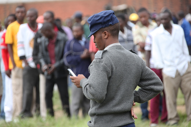 A police officer chats on a mobile phone at a polling station during a referendum in Harare, Zimbabwe, Saturday, March, 16, 2013. (AP Photo/Tsvangirayi Mukwazhi)